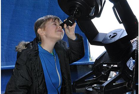 Young boy looking through telescope